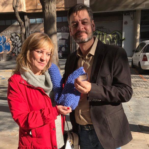 Galiana pasa a Hernández una bufanda solidaria.